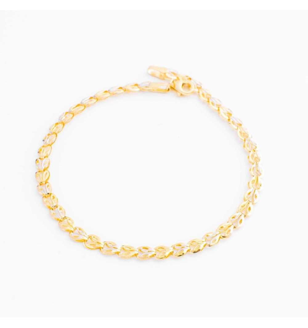 Złota bransoleta z fasetkowanymi wstawkami z białego i żółtego złota