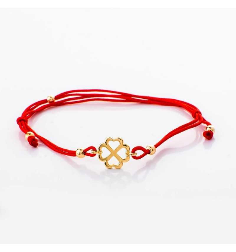 Złota bransoletka z koniczyną na czerwonym rzemyku