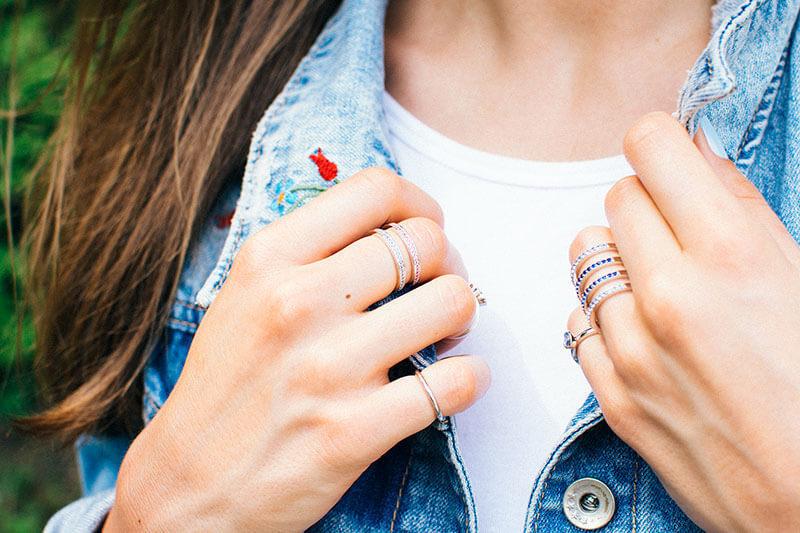dłonie w licznych drobnych pierścionkach pierścionek z niebieskimi cyrkoniami pierścionek tunel